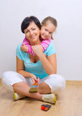 Woman with girl on the floor — Stock Photo