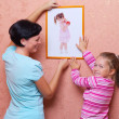 Young woman with girl hanging up a picture — Foto Stock