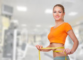 Mujer deportiva con centímetro cinta — Foto de Stock