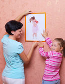 Young woman with girl hanging up a picture — Stock Photo