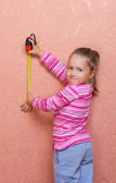 Little girl with measurement tape — Stock Photo