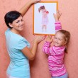 Woman hanging up picture with little girl — Stock Photo #13673767