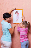 Woman with girl hanging up a picture — Stock Photo