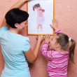 Woman and girl hanging up the picture — Stock Photo #14245817