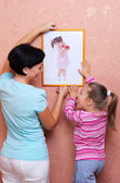 Woman and girl hanging up the picture — Stock Photo