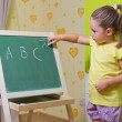 Girl writing letters on blackboard — Stock Photo #15659273