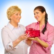 Young woman giving gift to her mother — Stock Photo