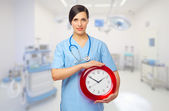 Doctor with clock at medical office — Stock Photo