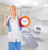 Smiling mature doctor with clock — Stock Photo