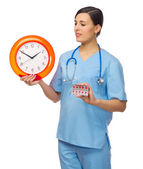 Doctor with clock and pills — Stock Photo