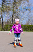 Little girl rides roller skates — Stock Photo