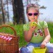 Foto Stock: Little girl eating apple at picnic