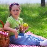 Little girl eating apple at picnic — Stock Photo #25469533