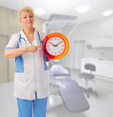 Mature doctor with clock — Stock Photo