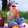 Little girl with plastic cup and picnic basket — Stock Photo