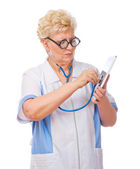Funny mature doctor listen tablet PC by stethoscope — Stock Photo