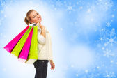 Girl with bags on blue snowy background — Stock Photo