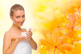 Young girl with body cream on autumnal background — Stock Photo