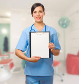 Young doctor with clipboard — Stock Photo