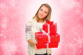 Young girl with gift boxes on winter background — Stock Photo