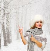 Jong meisje toont wijzende gebaar op besneeuwde forest — Stockfoto