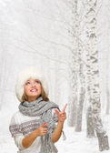 Girl shows pointing gesture at winter forest — Foto de Stock