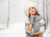 Young woman in fur hat at forest — Stock Photo