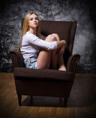 Young girl sit in chair on grey wall background — Stock Photo