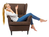 Young woman talking by mobile phone in chair — Stock Photo