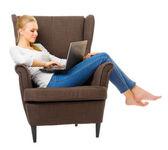 Jong meisje in spijkerbroek op stoel met laptop — Stockfoto