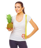 Smiling girl with pineapple and measurement tape isolated — Stock Photo