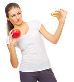 Young healthy woman with apple and hamburger — Stock Photo