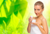 Woman with body cream on floral background — Stock Photo
