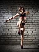 Mujer muscular en pared de ladrillo (versión oscura) — Foto de Stock