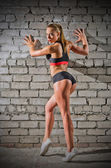 Muscular woman on brick wall background (normal version) — Stock Photo
