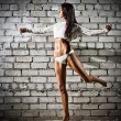 Young dancing woman on brick wall background (dark version) — Stock Photo #47934921