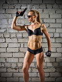 Muscular woman with gun on brick wall (normal version) — Stock Photo