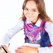 Smiling girl doing homework isolated over white backgorund — Stock Photo #12739401