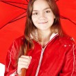 Smiling girl dressed in raincoat holding umbrella — Stock Photo