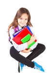 Miling girl sitting with backpack and books over white — Stock Photo