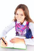 Smiling girl doing homework isolated over white backgorund — Stock Photo