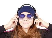 Girl listening music by headphones over white — Stock Photo