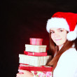 Smiling christmas girl holding presents over dark — Stock Photo