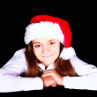 Smiling girl in christmas hat over dark — Stock Photo