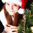 Smiling girl with christmas tree over dark — Stock Photo