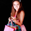 Smiling girl holding bags over dark — Stock Photo #13867594