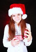 Girl in christmas hat holding gift over dark — Stockfoto