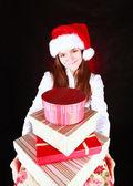 Smiling girl holding presents over dark — Stock Photo