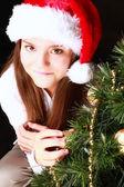 Smiling girl with christmas tree over dark — Stock Photo