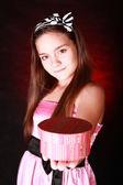 Smiling girl holding present over dark background — Stock Photo